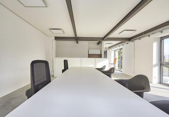 Konferenztisch mit Bürodrehstühlen und Hartschalenstühlen